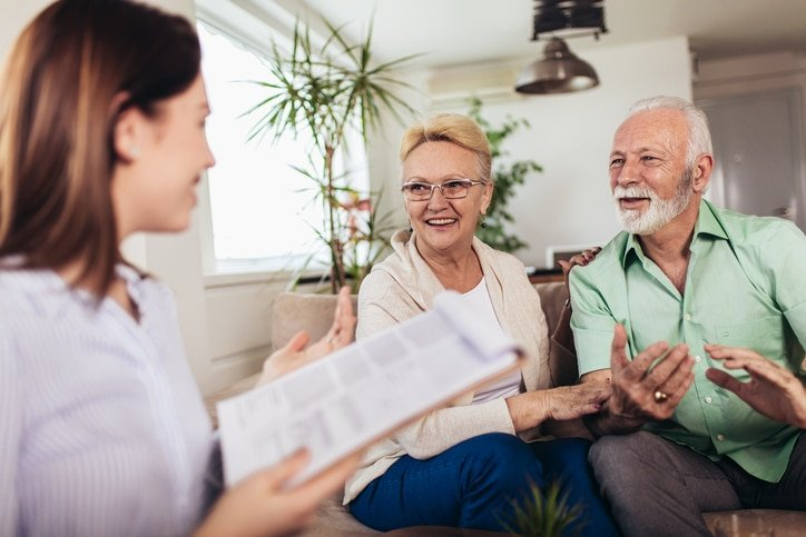 Positive aged couple consulting with senior living community agent