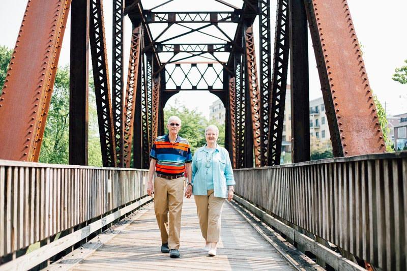 Ellen & Lewis Jones, walking along an old bridge holding hands