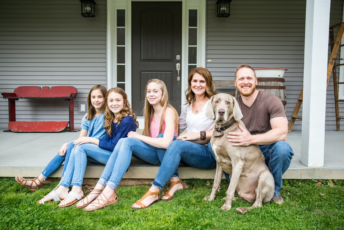 The Morgans, Customer Testimonial, photo of family on a porch with their dog.