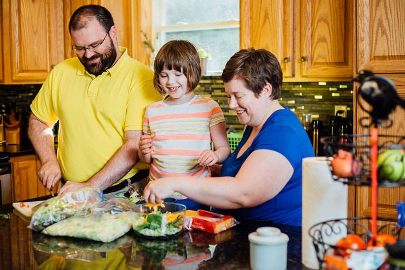 Family in kitchen making dinner together