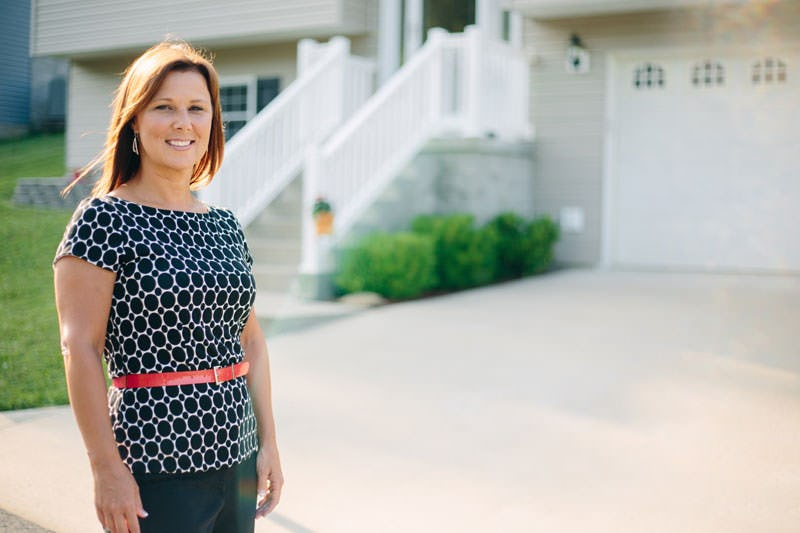 Leslie Harclerode standing in front of her new home