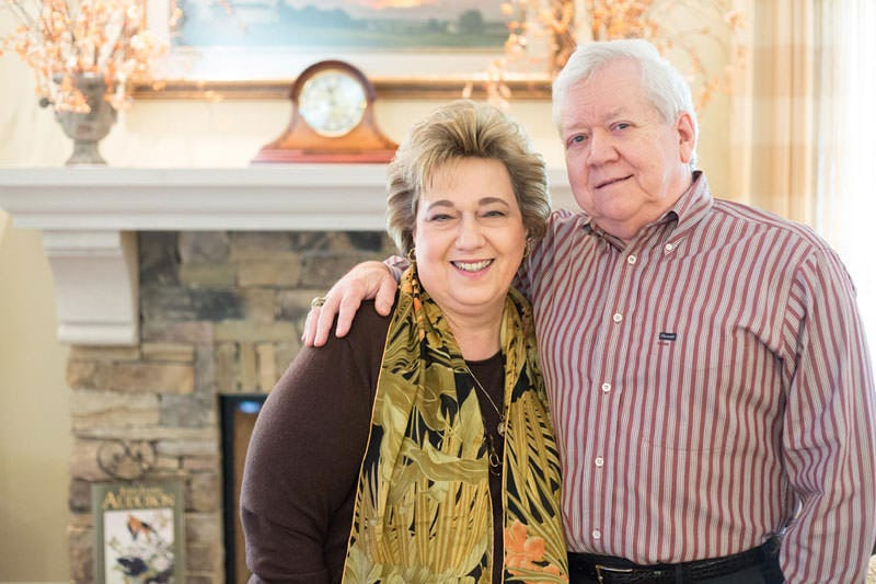 Piteleski couple standing in new home, in front of the fireplace with husbands arm around wife.